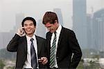 Chinese man, parlait au téléphone tandis que les textes de l'homme de race blanche.