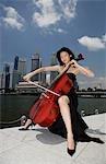 Femme chinoise joue du violoncelle à l'extérieur de bâtiments
