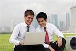 Homme chinois et caucasienne regardant ordinateur portable sur le côté