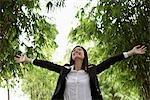 Jeune femme vêtu d'un costume et levant son bras vers le haut à l'extérieur