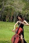 Femme joue du violoncelle, entouré par la nature