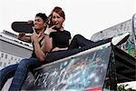 Young couple sitting on graffiti wall.