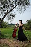 Femme tenant le violoncelle à l'extérieur sous un arbre