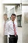 Businessman standing between reflective columns, three quarter length