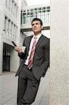 Businessman leaning against wall, three quarter length