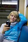Jeune femme à l'aide de téléphone portable en train de la ville, vue de face