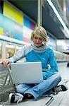 Jeune femme avec ordinateur portable à la gare de la ville, vue de face