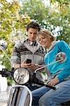 Deux adolescent avec cyclomoteur avec GSM, taille haute
