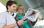 Couple adolescent, lire le journal sur le pouce, vue de dessous