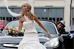 Braut vor ein Auto, Bräutigam im Hintergrund