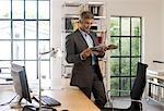 Homme lisant un magazine dans un bureau
