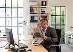 Homme lisant un journal, à son bureau