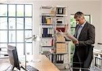 Homme lisant un journal dans un bureau
