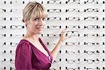 A mid adult woman choosing a pair of eyeglasses in an eyewear store