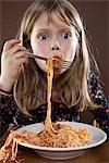 A young girl eating spaghetti messily, studio shot