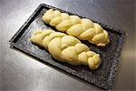 Deux pains tressés qui attendent d'être cuit au four
