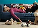 Haute femme endormie sur le canapé avec des jouets