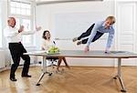 Homme d'affaires sautant par-dessus la table