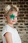 Junges Mädchen mit grünen Sterne Bemalung über Auge