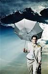 Kaufmann holding einen Regenschirm und Wandern