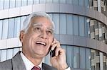 Homme d'affaires parlant sur un téléphone mobile et souriant