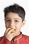 Portrait of a boy eating laddu