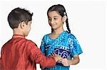Girl tying rakhi on the wrist of her brother