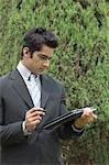 Homme tenant un ordinateur portable dans un parc