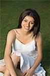 Frau sitzt in einem Park und Lächeln
