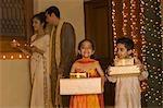 Enfants tenant des cadeaux avec leurs parents tenue religieuse offrant en arrière-plan
