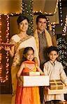 Enfants tenant des cadeaux avec leurs parents tenant une offrande religieuse