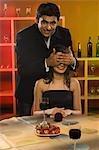 Homme qui couvre les yeux de sa petite amie dans un bar