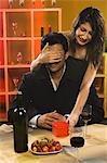 Femme couvrant les yeux de son petit ami dans un bar