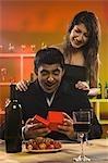 Femme donnant un cadeau à son petit ami dans un bar