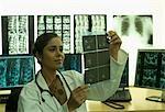 Femme médecin examinant un rapport aux rayons x