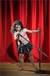 Mädchen auf einer Bühne in ein Mikrofon singen