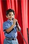 Schüler, die in ein Mikrofon singen, auf einer Bühne