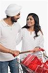 Couple pushing a shopping cart of gifts
