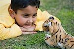 Junge spielt mit einem Stofftier in einem park