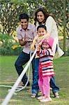 Paar mit ihren Kindern spielen Tauziehen in einem park