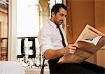 Businessman in hotel room reading newspaper