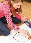 Girl kneeling on floor painting with watercolours