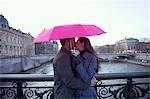 Couple kissing under a pink umbrella on a bridge over the Seine river, Paris, France