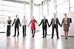Geschäftsleute, die Hand in Hand im Büro