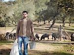 Man on farm holding bucket and bag