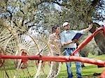 Man and woman on farm with hay rake