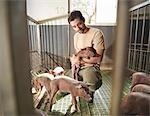 Man in pig pen holding a piglet