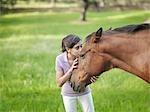 Girl kissing horse on forehead