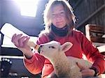 Woman feeding lamb with bottle