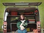 Woman sitting in van boot holding lamb